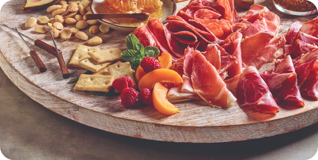Charcuterie board with prosciutto, crackers, almonds and fruit