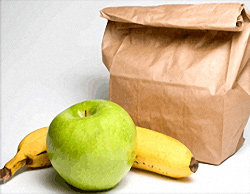 Brown bag lunch with a banana and green apple